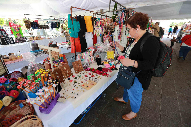 Mujer asistente, a la Feria, observando una de las artesanías expuestas por una región indígena.