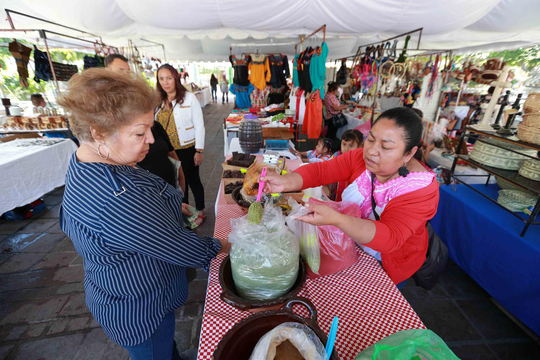 Mujer expositora indígena, sirviendo pasta para hacer mole verde para una compradora asistente a la feria.