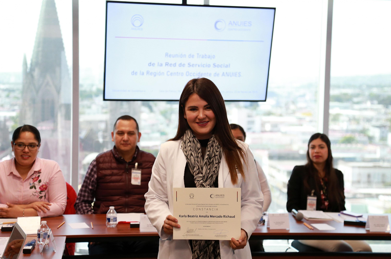 Karla Beatriz Amalia Mercado Richaud sostiene el reconocimiento impreso que le fue entregado en la presentacion