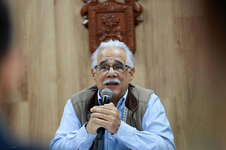 El doctor Eduardo Santana Castellón hablando al microfono el cual sostiene con sus dos manos
