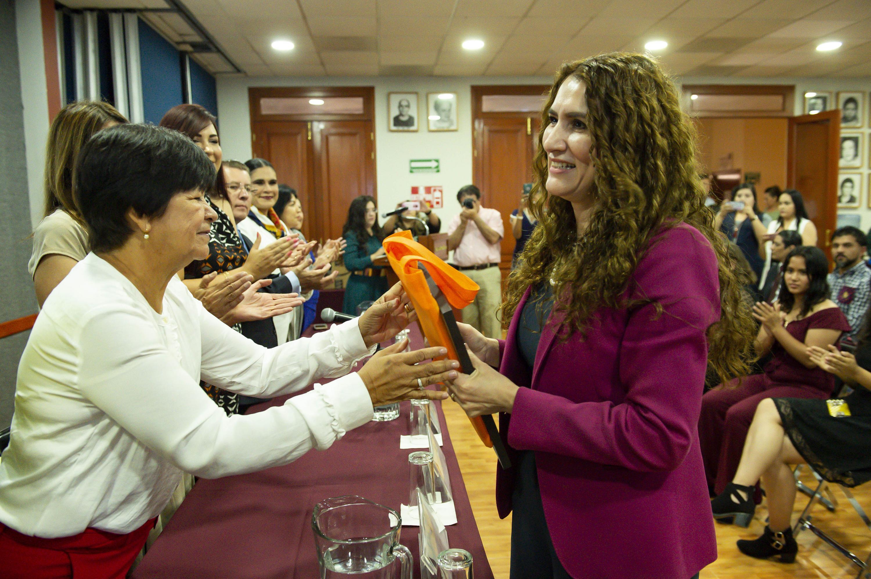 Una de las universitarias recibe de mano de la mesa de presidum el reconocimiento
