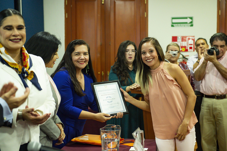 Una de las jovenes reconocidas recibe un reconocimiento impreso y lo muestra a la camara
