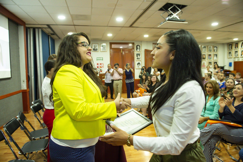 La doctora Laura Fong entrega un reconocimeinto a una de las mujeres distinguidas