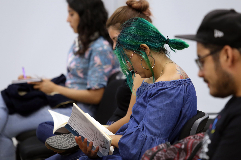 Asistente a la presentación leyendo el libro