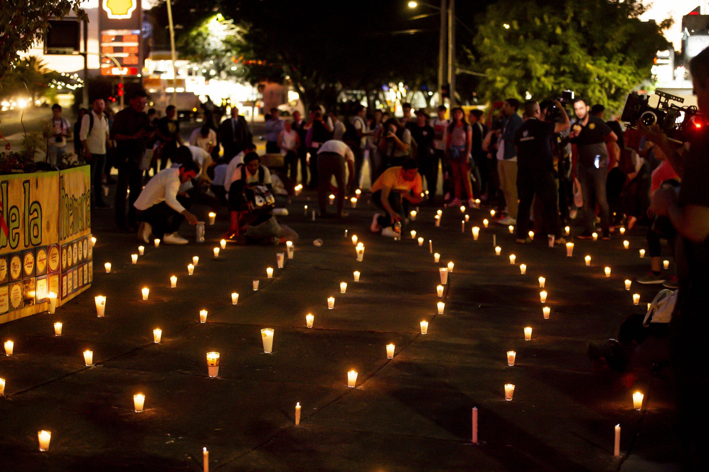 Asistentes a la marcha colocando veladoras en la glorieta de las y los desaparecidos en la avenida Niños Héroes.