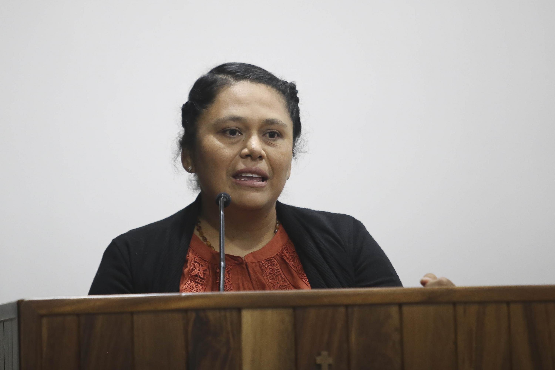 La investigadora hablando al micrófono desde el presidium