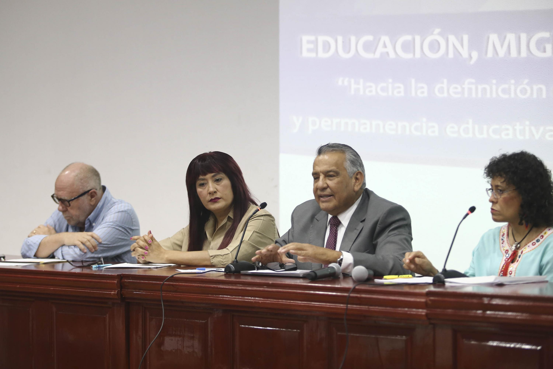 cuatro academicos sentados en la mesa de presidium del Foro de Migracion
