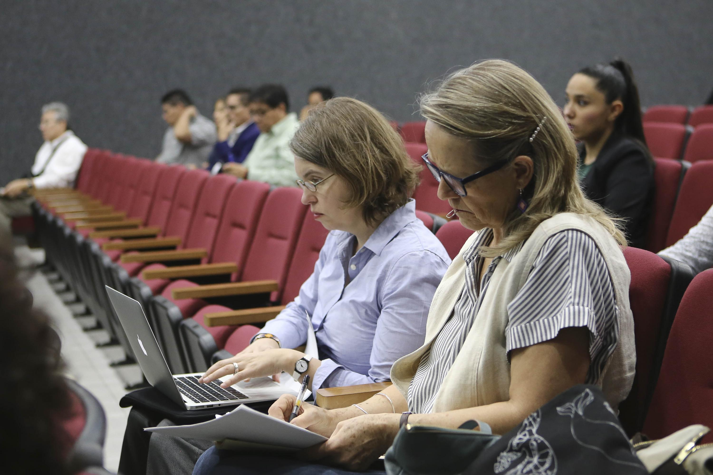 Dos academicas presentes en el auditorio tomando nota desde su asiento