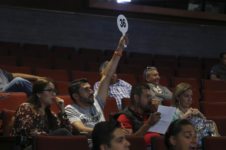 Participante adscrito a la subasta alzando su paleta de ofrecimiento