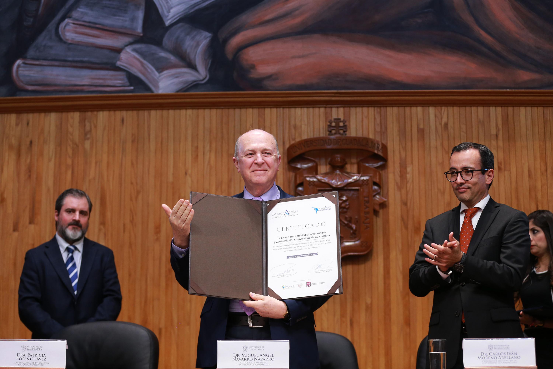 Rector General de la UdeG, doctor Miguel Ángel Navarro Navarro, mostrando los certificados de acreditación.