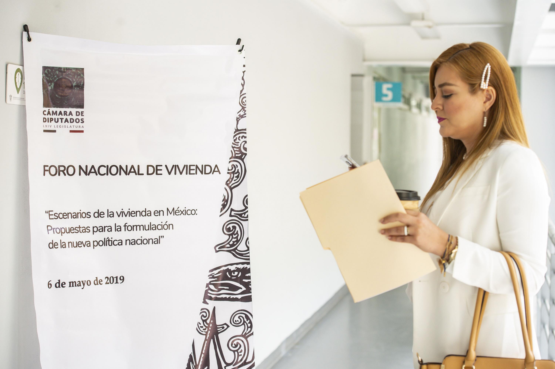 Asistente al foro nacional, revisando su teléfono celular fuera de la vídeo aula del Centro Universitario de Arte, Arquitectura y Diseño (CUAAD)