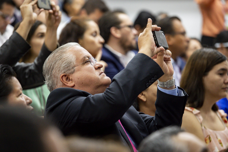 Asistente al Foro Nacional de Vivienda 2019, tomando fotografías con su teléfono celular