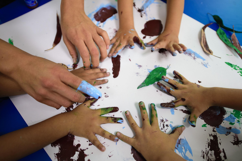 Infantes con sus manos pintadas, plasmando un mural