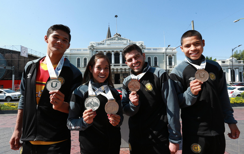 Atletas representantes de la Universidad de Guadalajara, en las disciplinas de atletismo, lucha grecorromana y box, mostrando sus medallas de oro