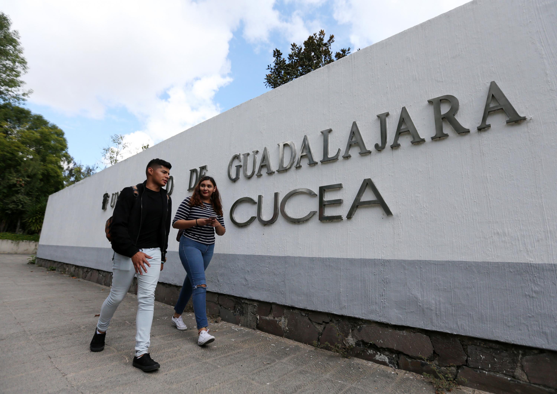 Dos estudiantes caminando por el Centro Universitario de Ciencias Económico Administrativas (CUCEA)