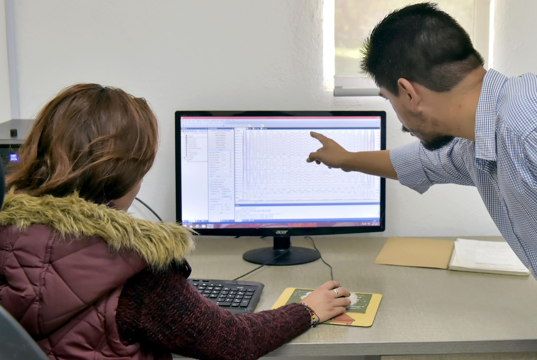 Profesor explicando a alumna, enfrente de una computadora