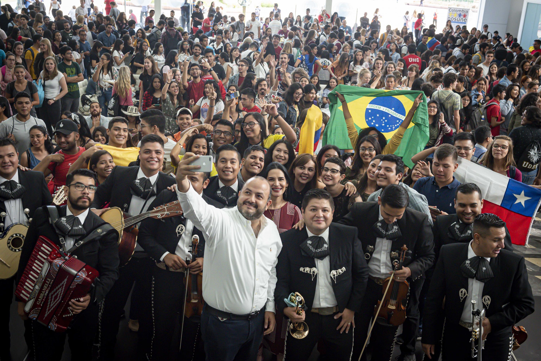 Rector General de la Universidad de Guadalajara, doctor Ricardo Villanueva Lomelí, tomando una selfie durante la ceremonia de bienvenida