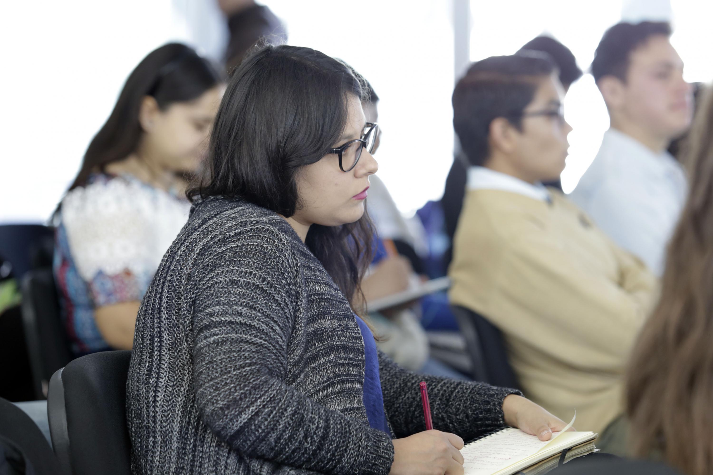 Alumna del Centro Universitario de Ciencias Sociales y Humanidades (CUCSH), tomando nota de la conferencia.