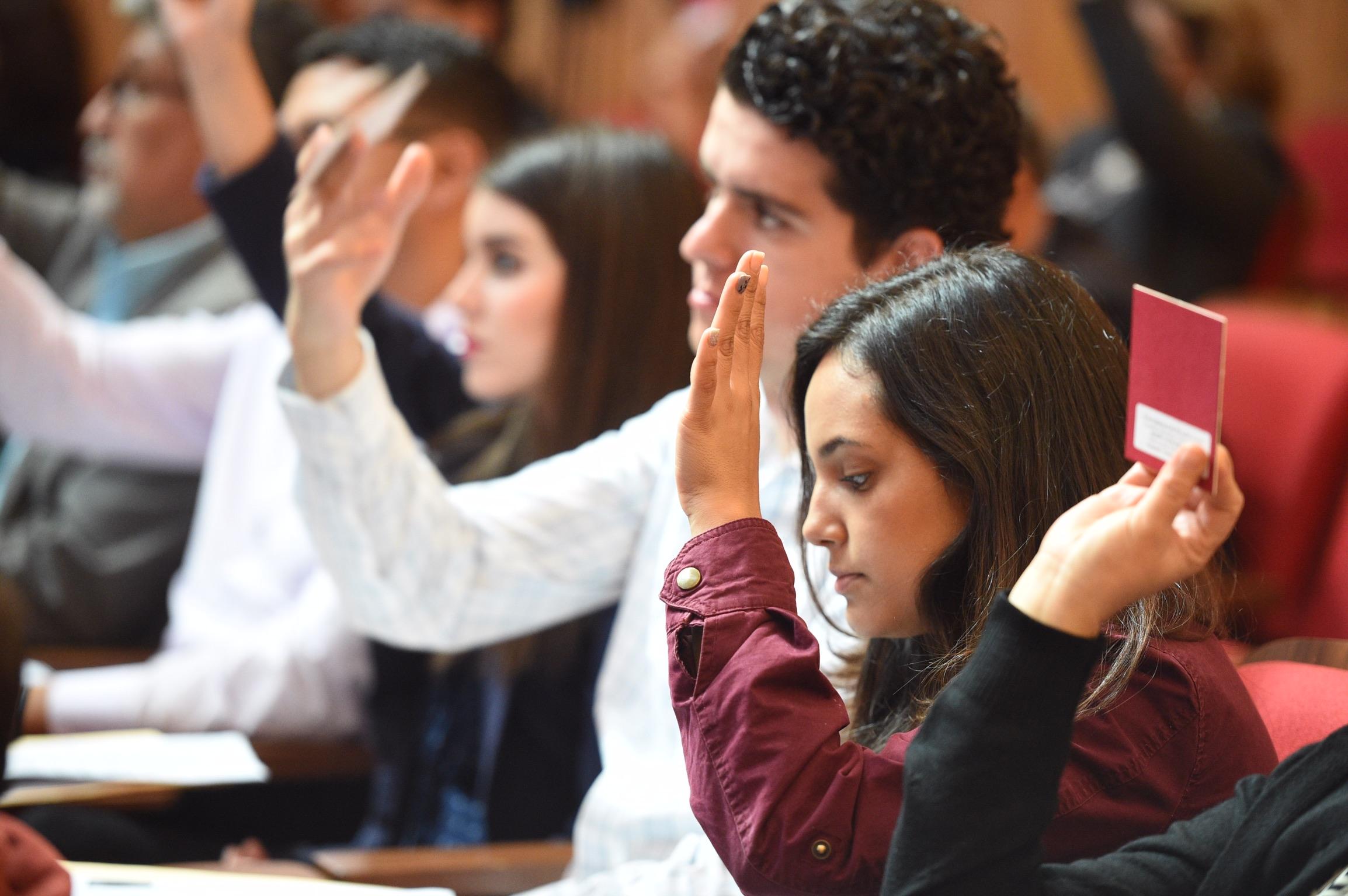 Jovenes consejeros levantan su mano para votar a favor de una propuesta en el Consejo General Universitario