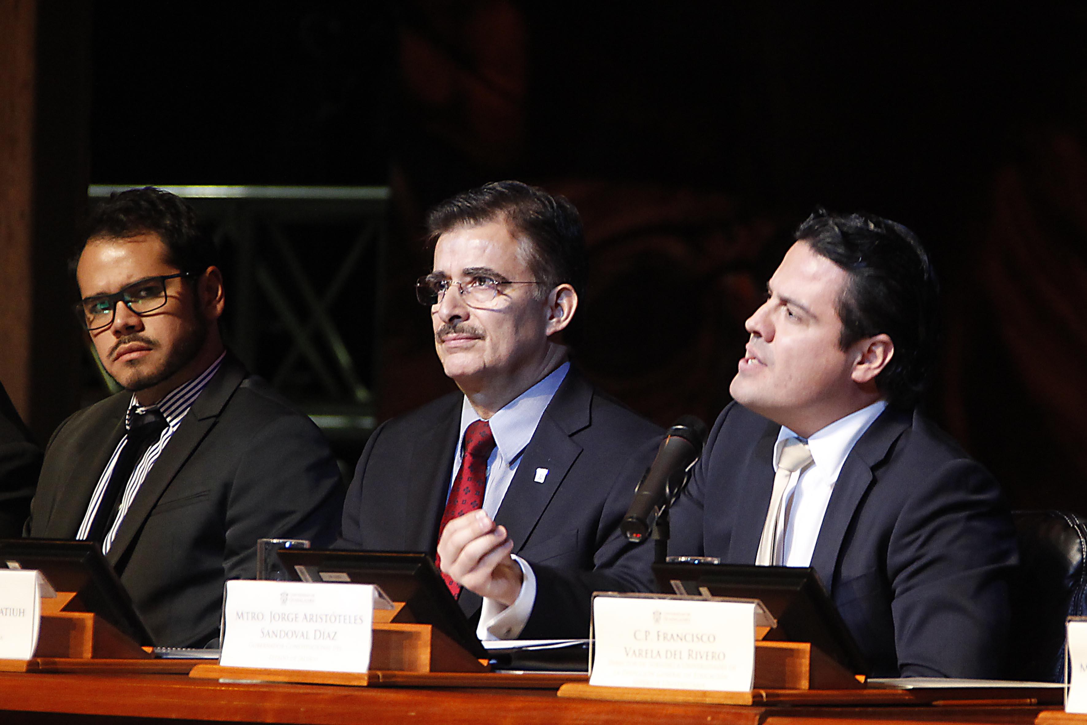 Maestro Jorge Aristóteles Sandoval Díaz, gobernador de Jalisco, con micrófono en panel, haciendo uso de la palabra, a un lado del Rector General de la Universidad de Guadalajara.
