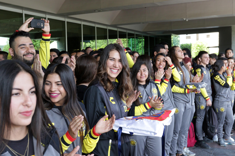 La atleta Alely Hernández Martínez sosteniendo la bandera de la UDG