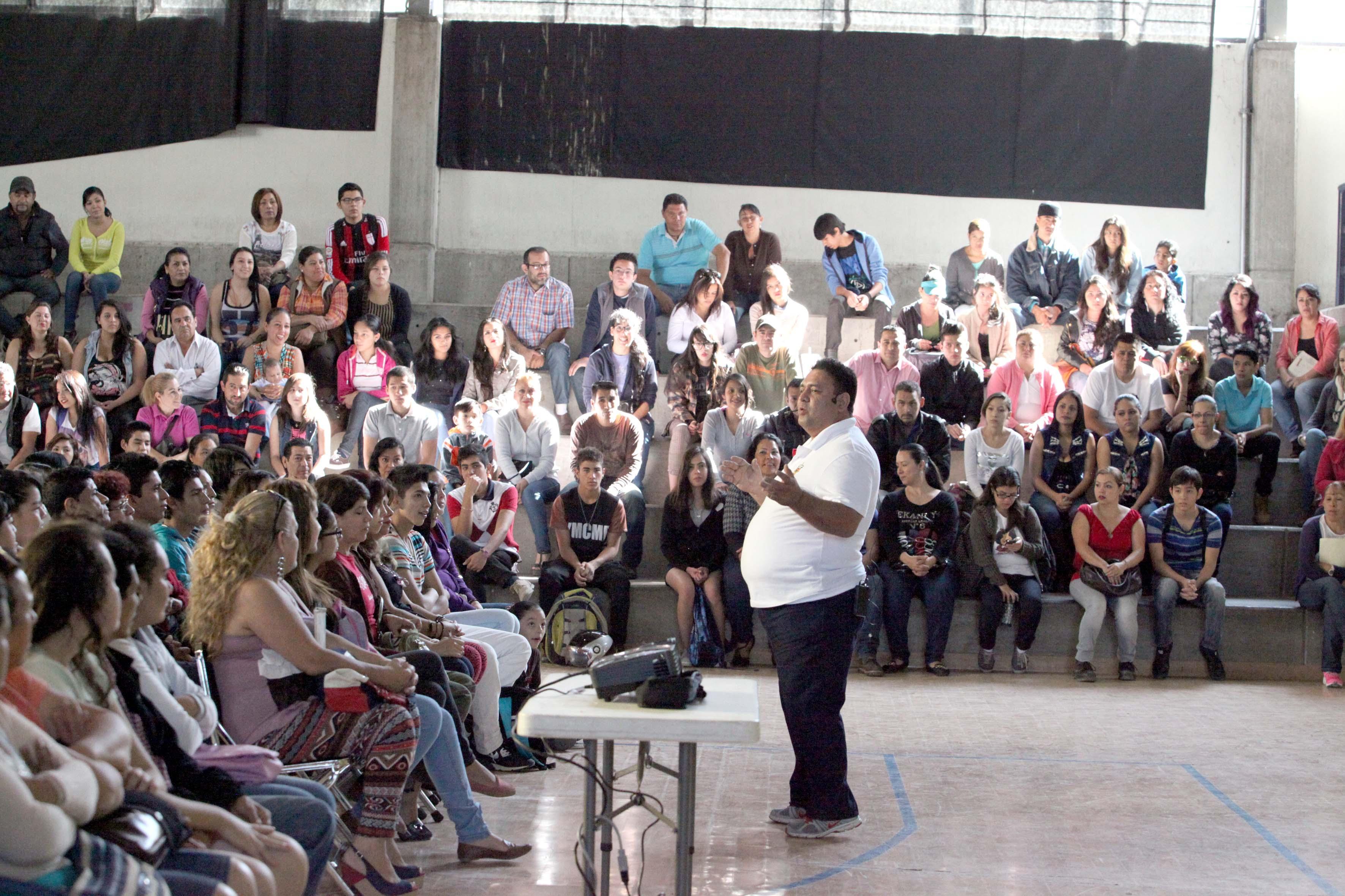 Grupo de gente reunida en un auditorio escuchando charla para prevenir violencia intrafamiliar