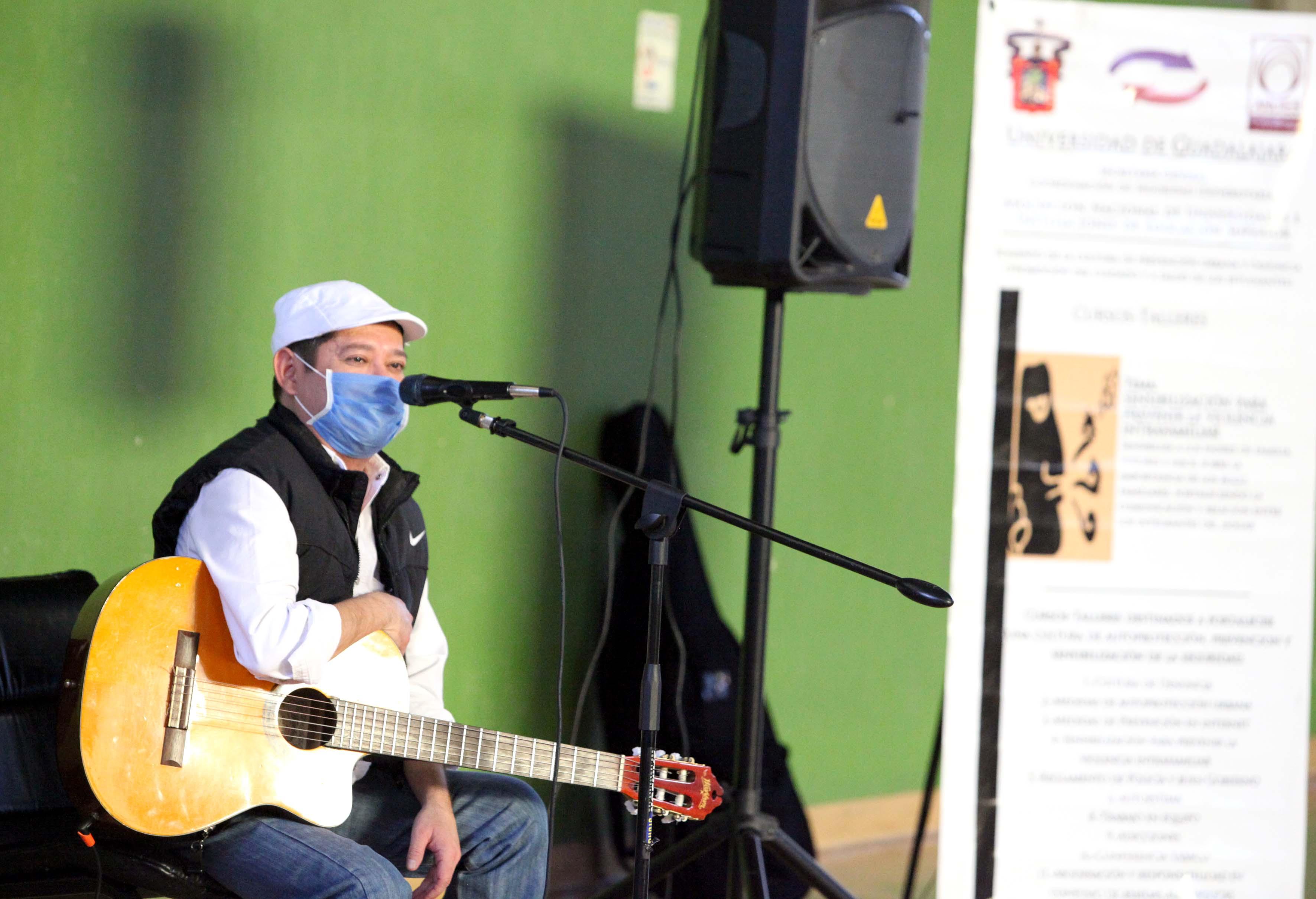 Hombre sentado con una guitarra en las manos, en el rostro lleva un cobre bocas