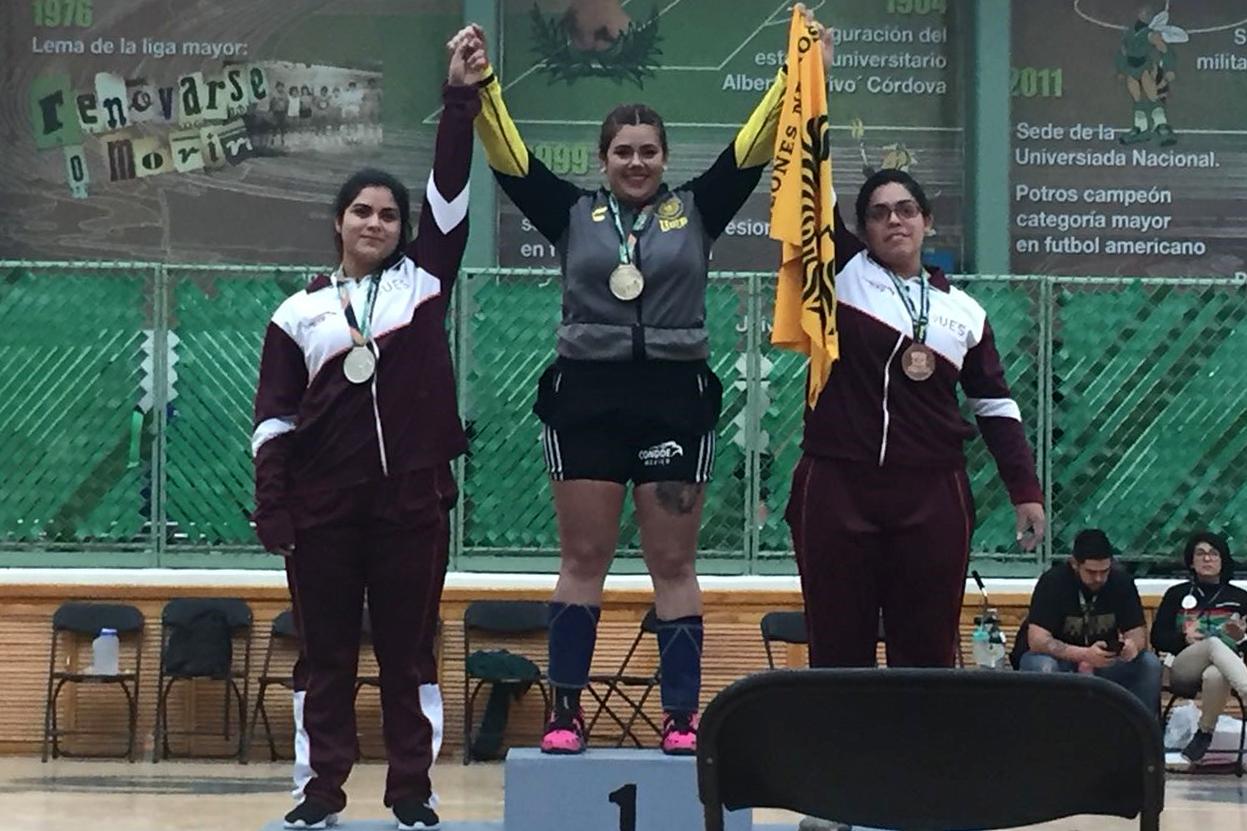 Estudiantes ganadoras de presea en la disciplina de levantamiento de pesas de la Universiada Nacional 2018,en podium con los brazos en alto, festejando su triunfo.