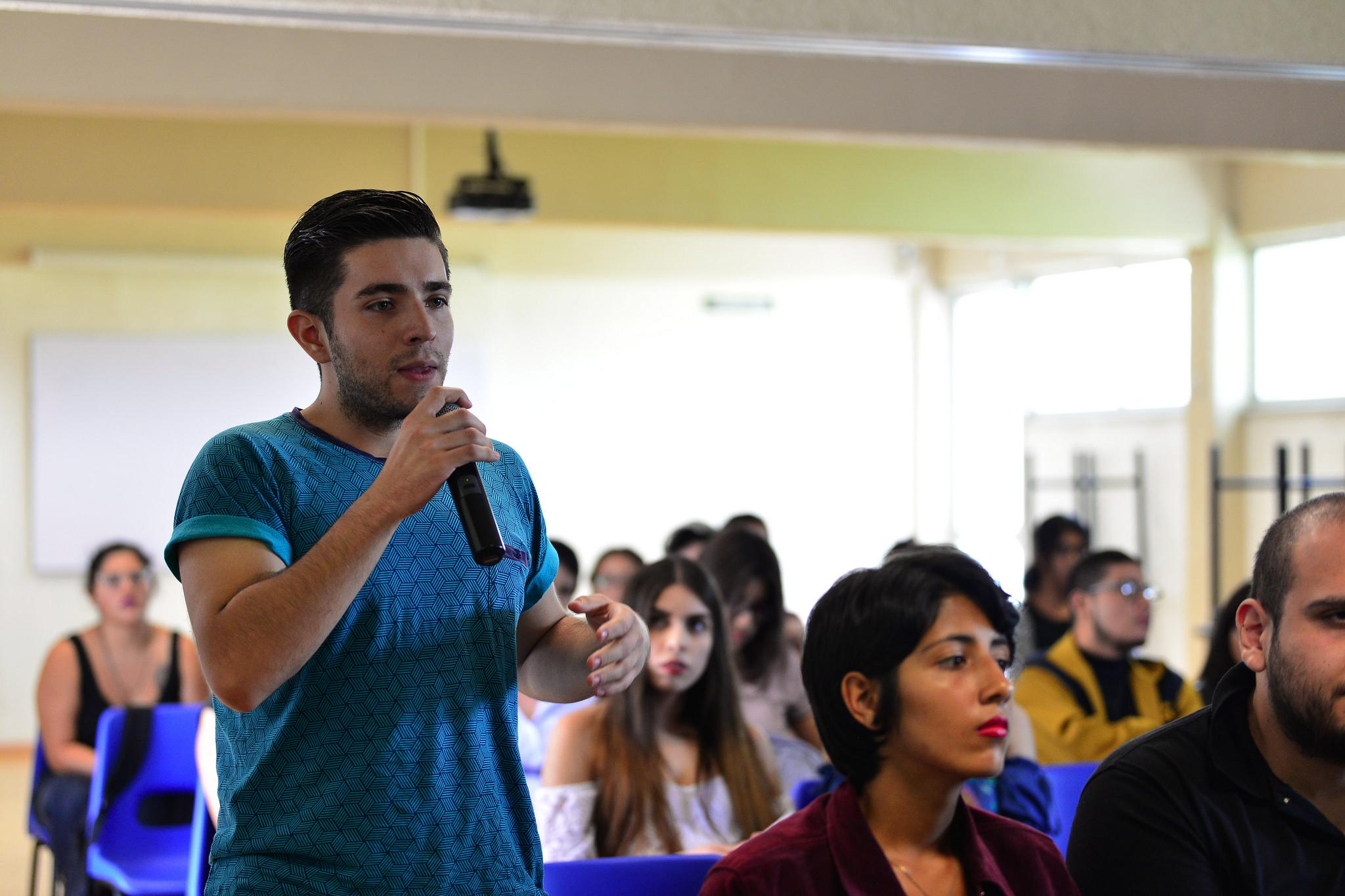 Estudiante del Cuciénega, asistente a la plática, con micrófono en mano, formulando una pregunta para la ponente.