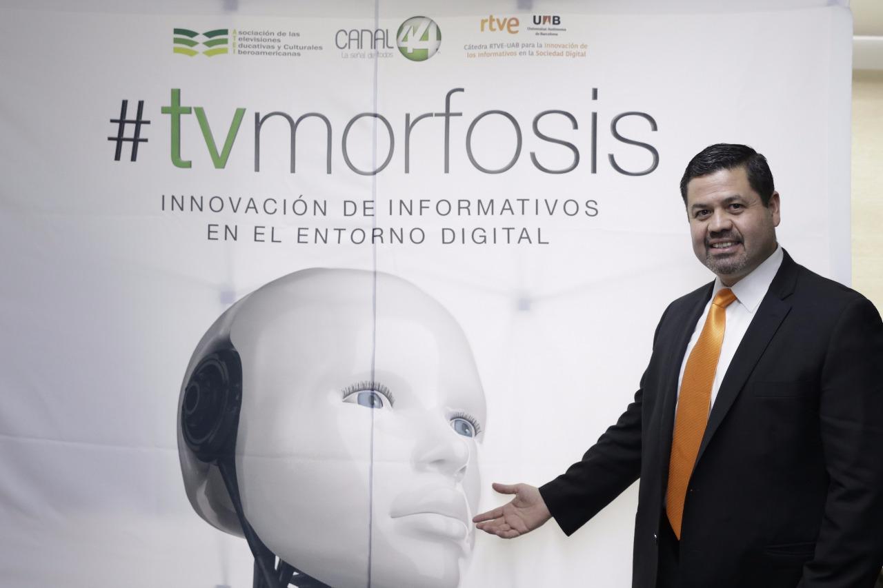 Mtro. Gabriel Torres Espinoza junto a cartel de TVMorfosis