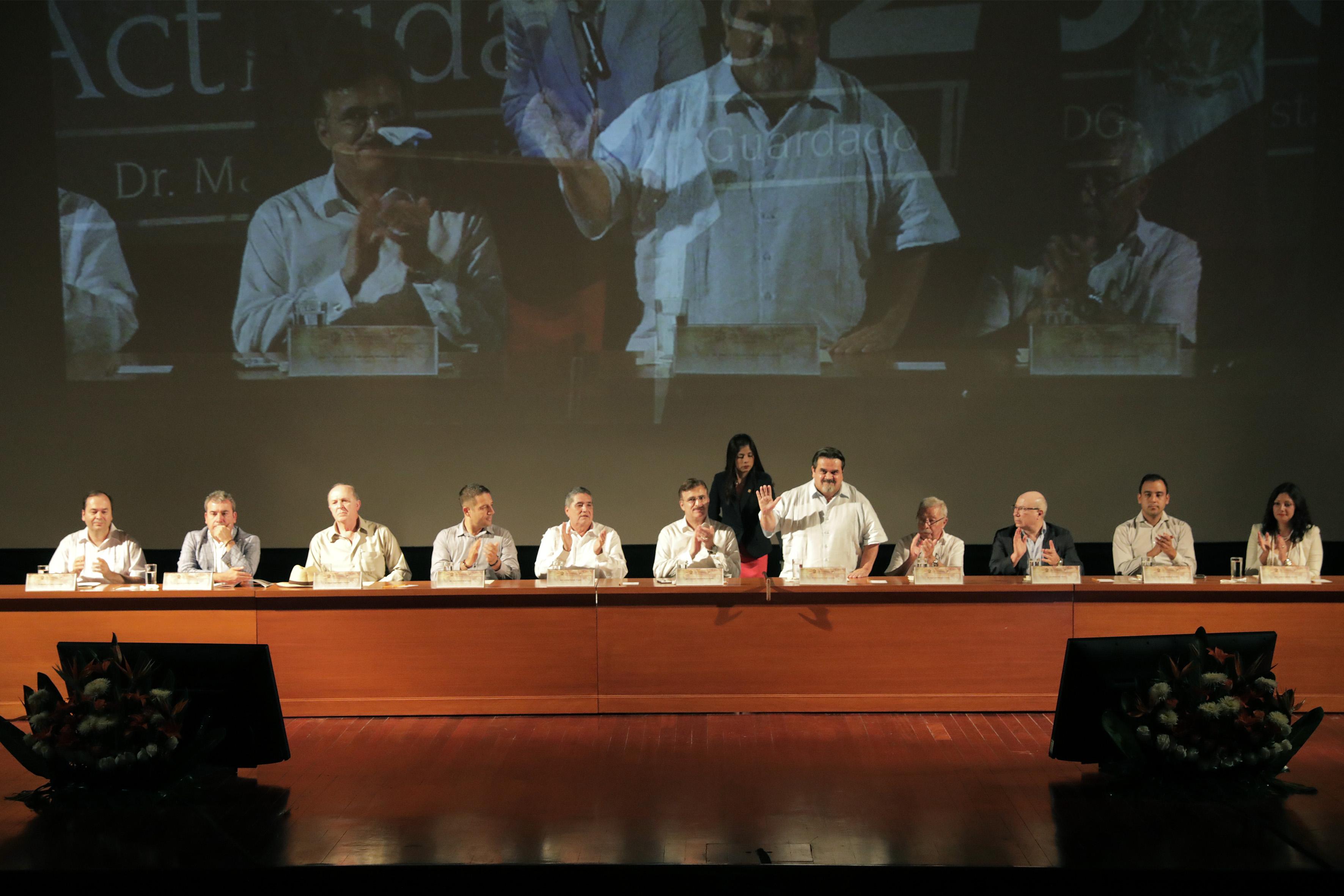 Rector del CUC, Marco Antonio Cortés Guardado, de pie saludando con la mano en alto al momento de la ceremonia de presentación durante su informe de actividades 2016; mientras panelistas invitados aplauden.