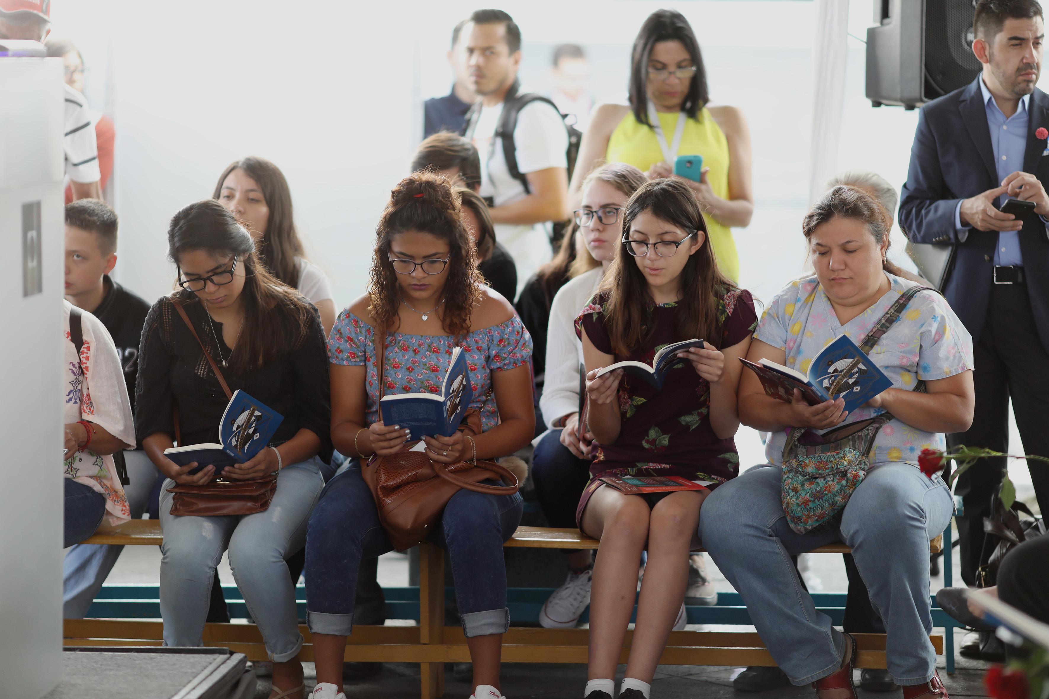 """Amantes de la lectura, asistentes al evento; leyendo el libro de """"Inéditos y Extraviados""""."""
