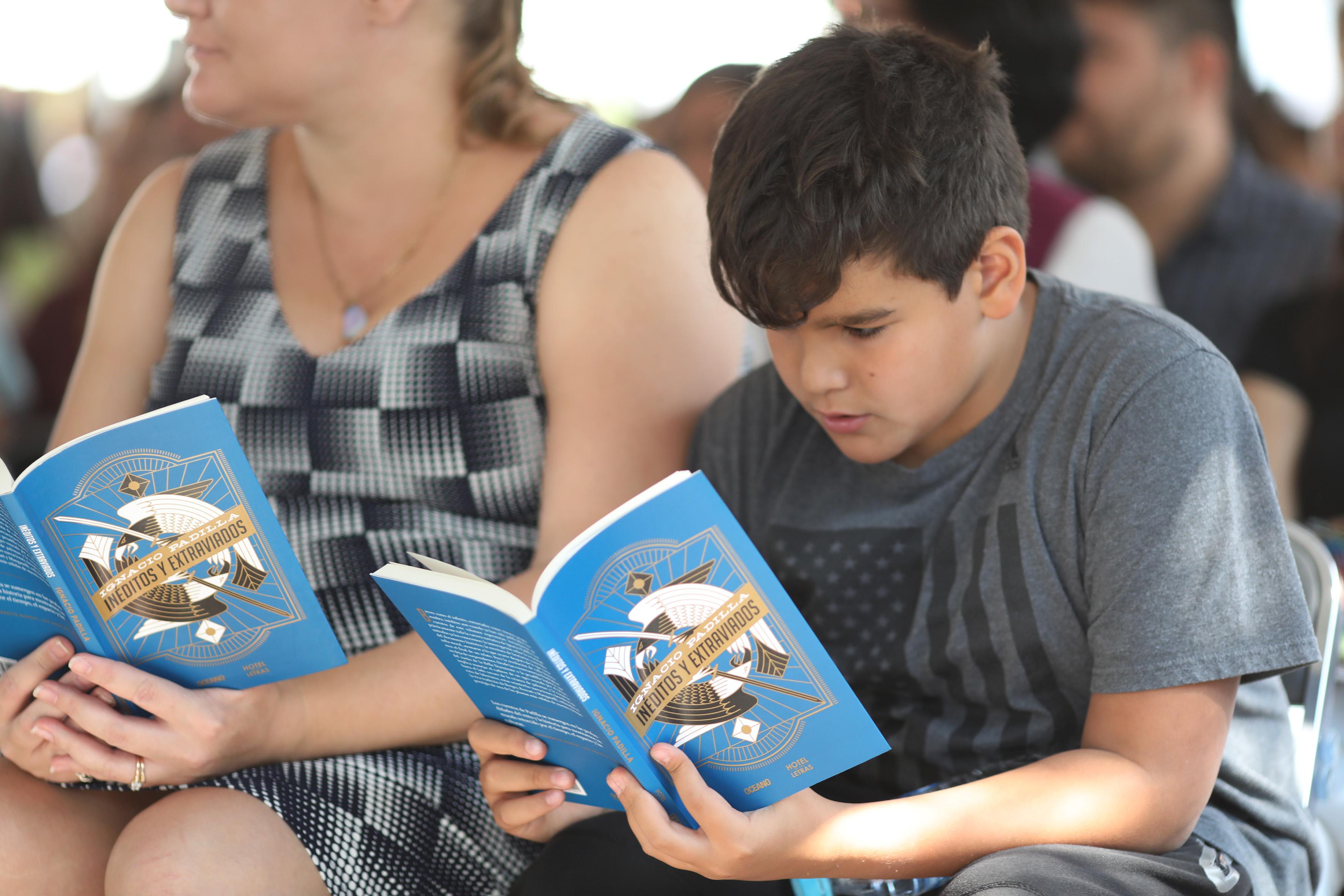 """Niño asistente al evento,leyendo el libro de """"Inéditos y Extraviados""""."""