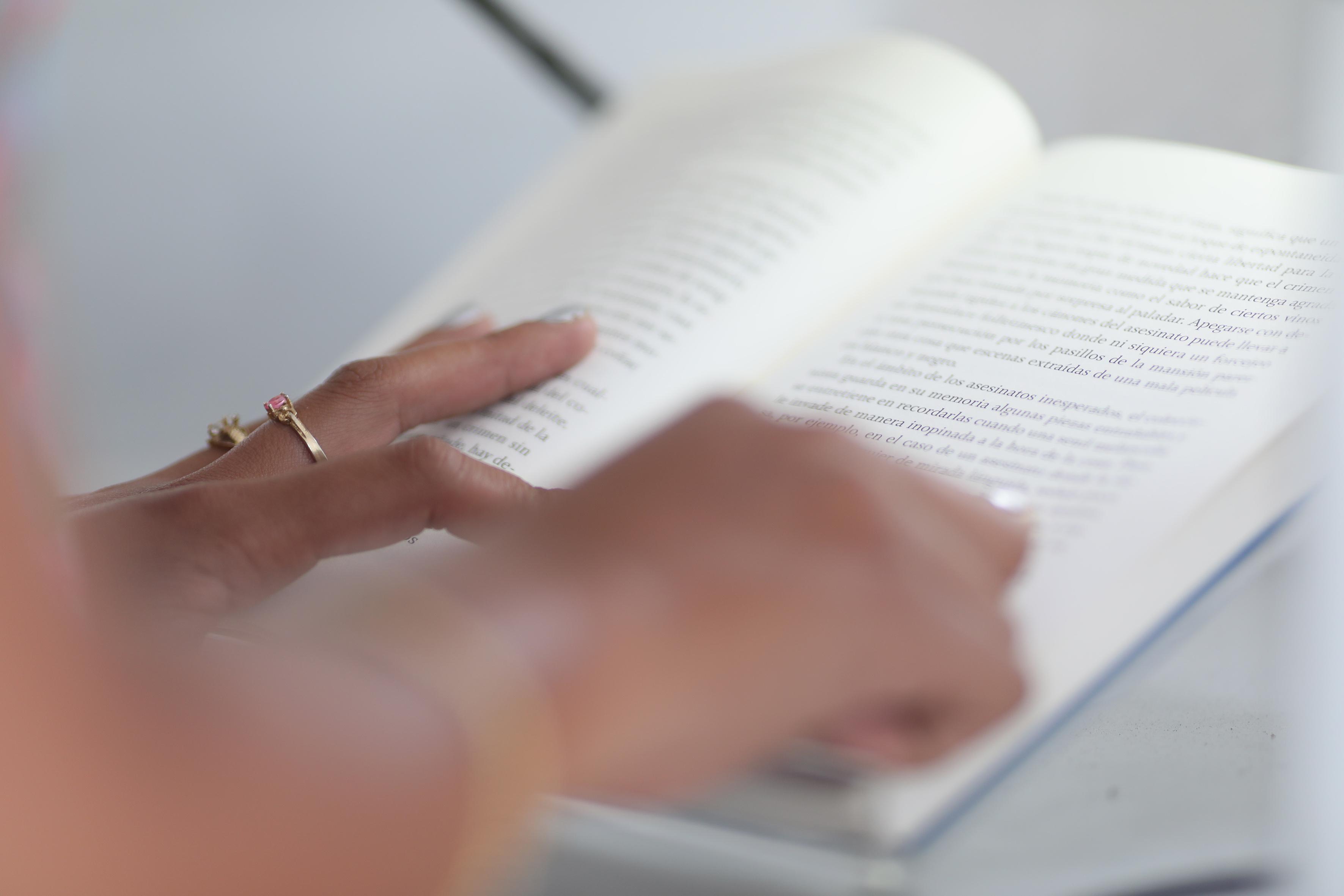 Mujer siguiendo la lectura del libro con su dedo índice.