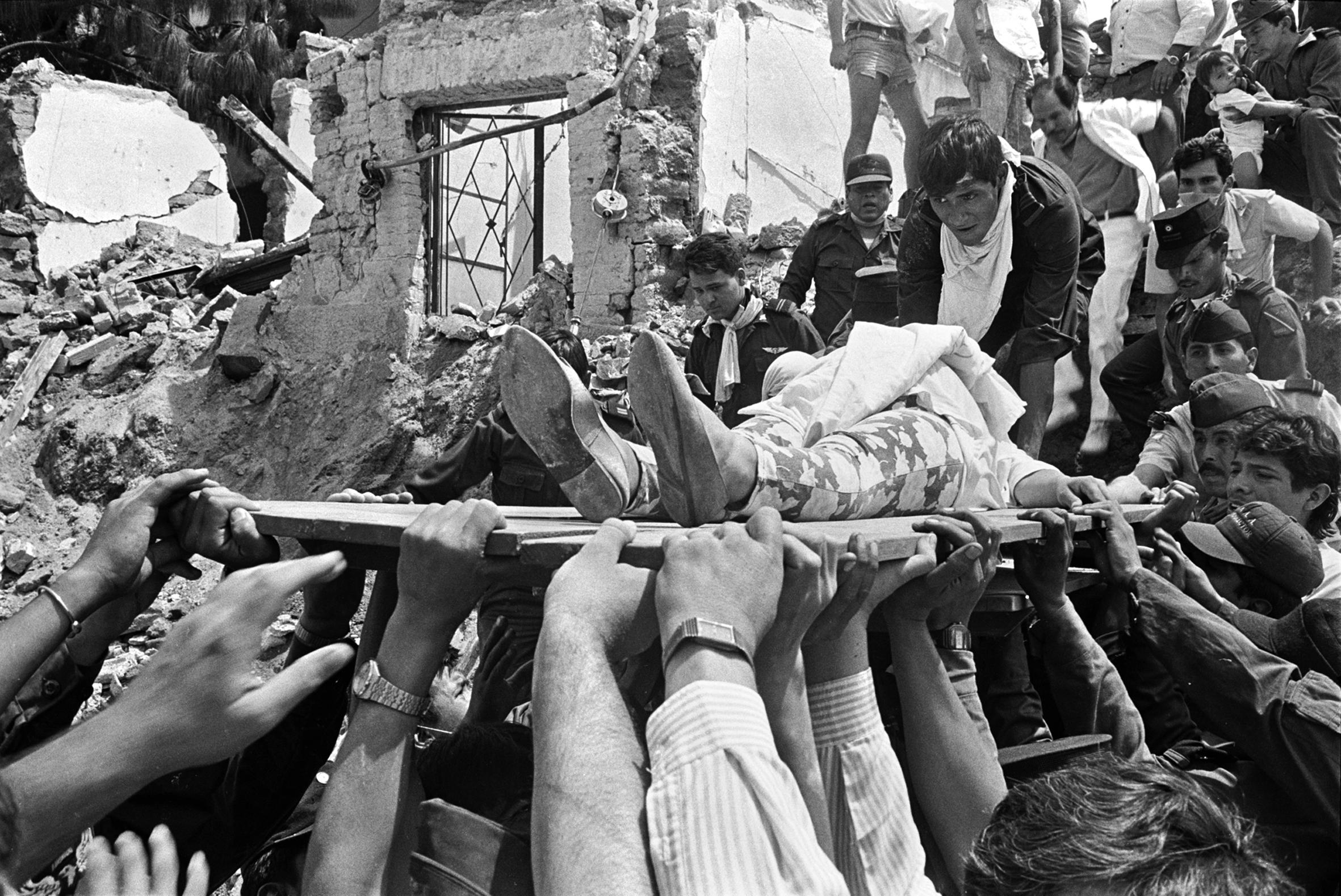 Civiles y rescatistas, transportando a un herido rescatado de los escombros, con una tabla como camilla improvisada.