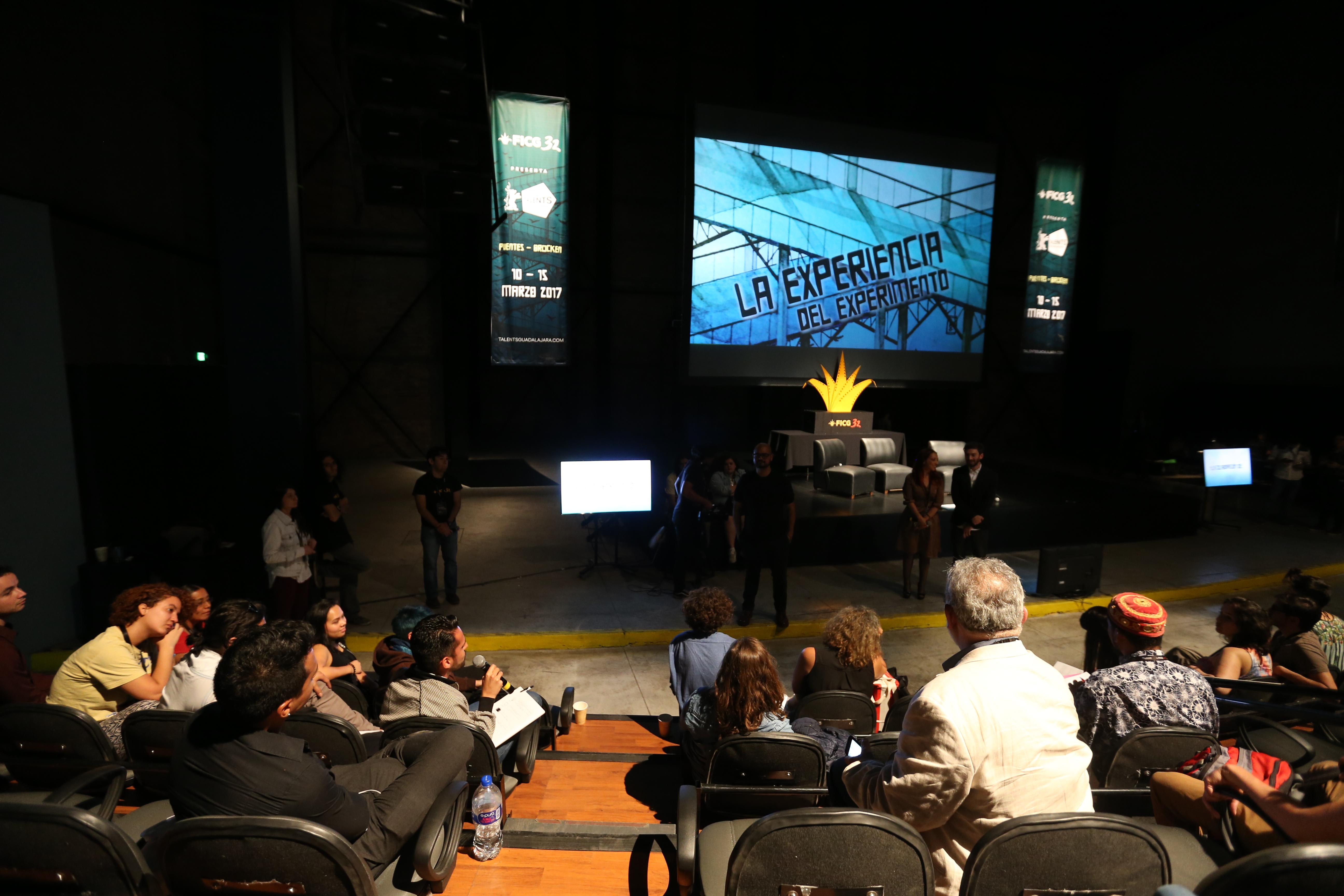 Persona asistente a la clausura de Talents Guadalajara, con micrófono en mano, realizando preguntas a los coodinadores y participantes del evento.