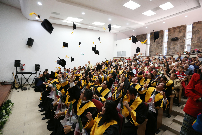 Estudiantes en evento de graduación en auditorio de la institución educativa