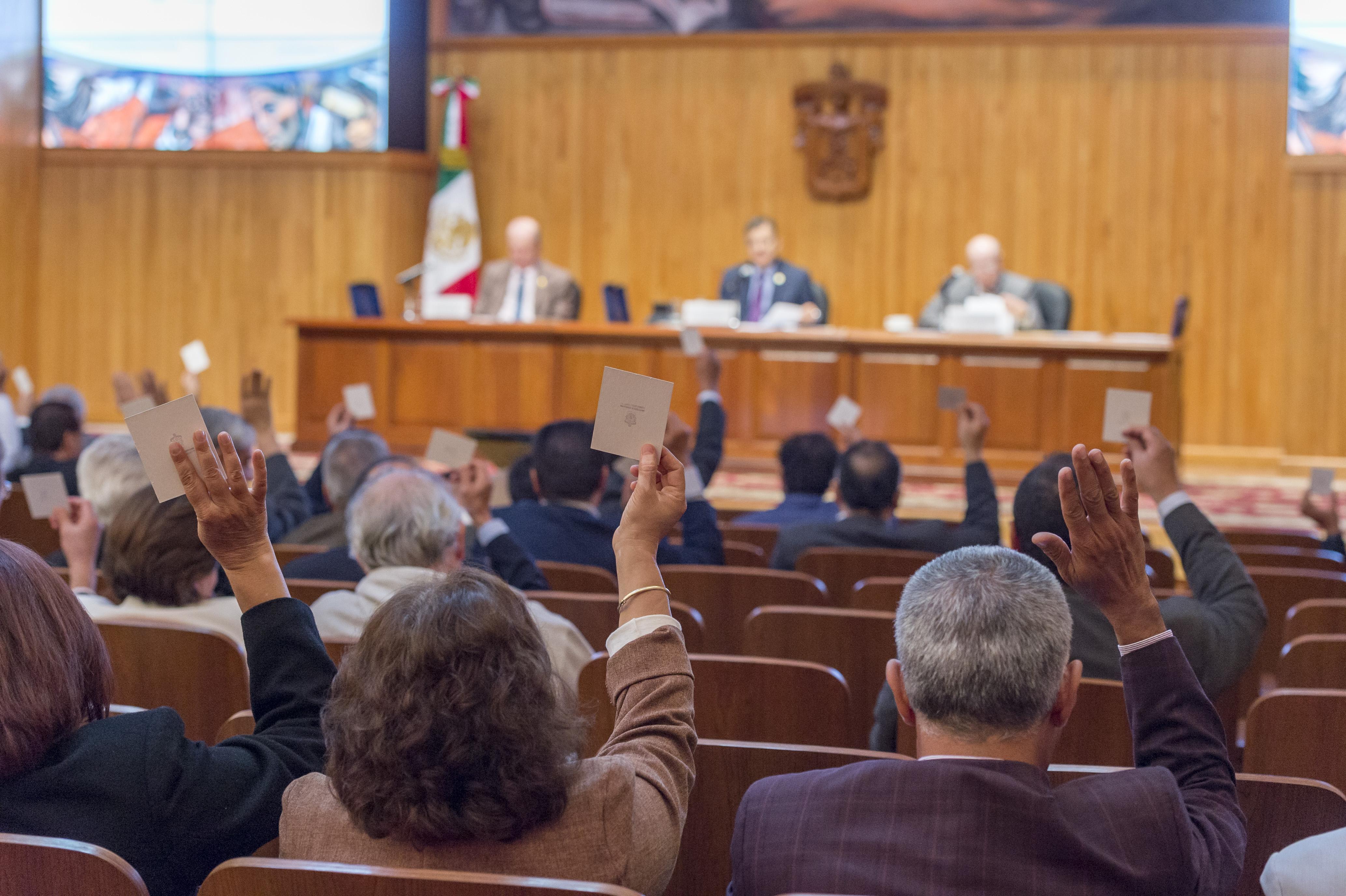 Sesión de Consejo General Universitario, vista al presidium y a los consejeros ejerciendo el voto.