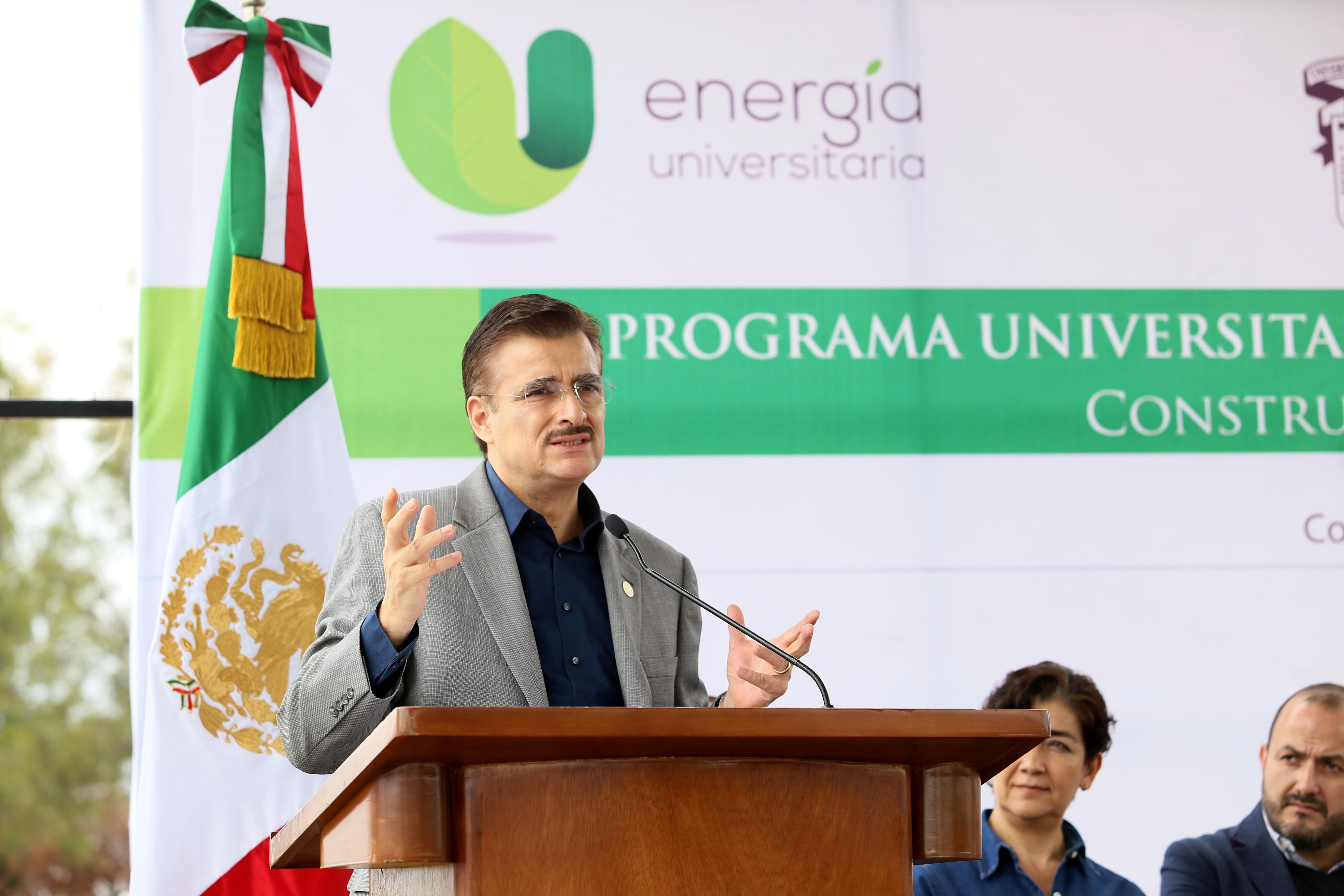 Maestro Itzcóatl Tonatiuh Bravo Padilla, Rector General de la Universidad de Guadalajara, con micrófono en podium haciendo uso de la palabra, durante inauguración de la primera pieza del huerto fotovoltaico.