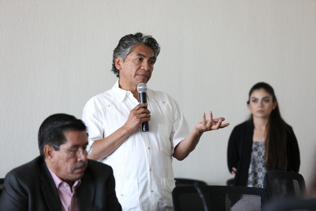 Miembro panelista participante en reunión de pie y con micrófono en mano haciendo uso de la palabra.
