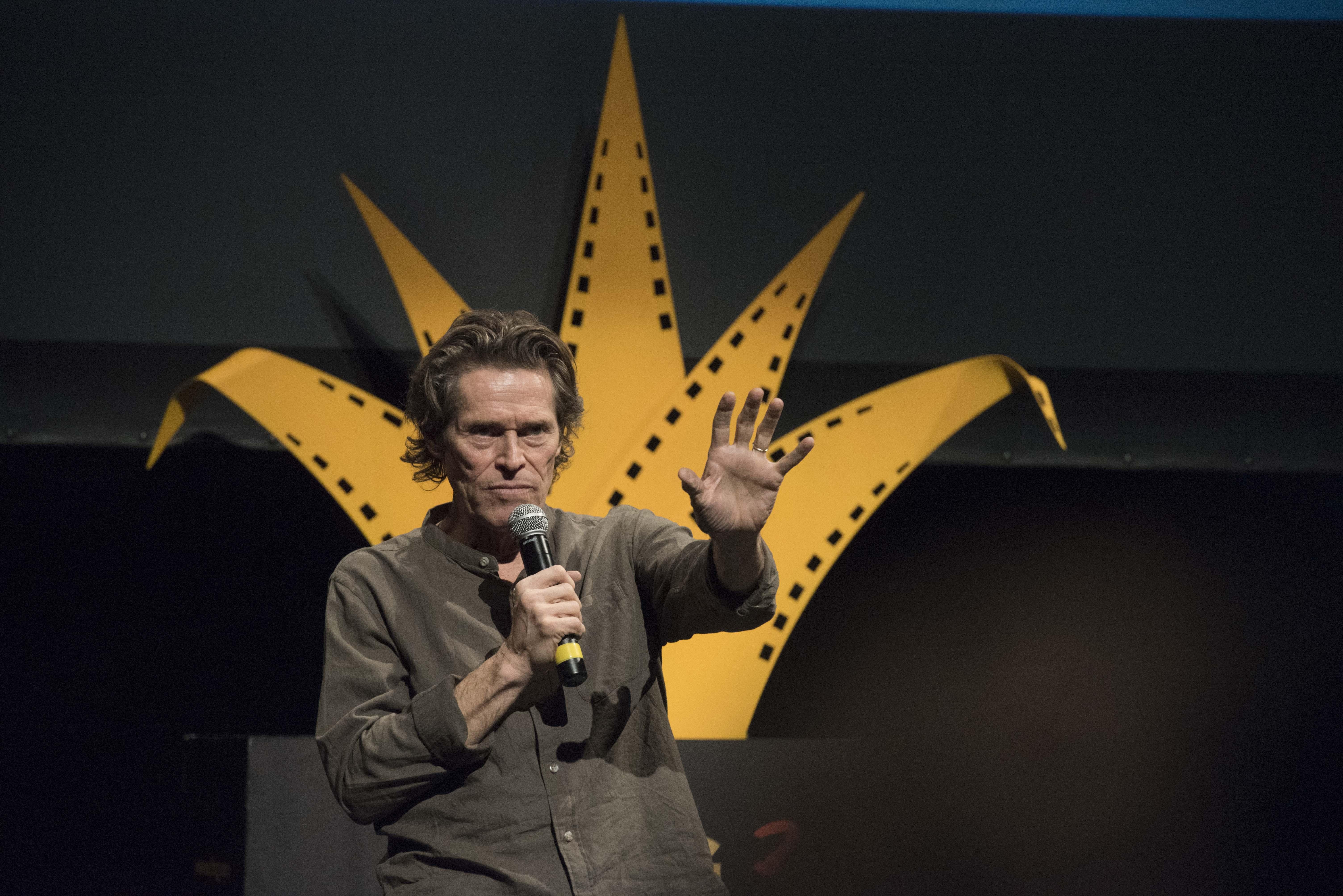 El actor estadounidense Willem Dafoe, con micrófono en mano, haciendo uso de la palabra.
