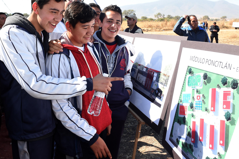Jovenes asistentes viendo de cerca los detalles del proyecto.