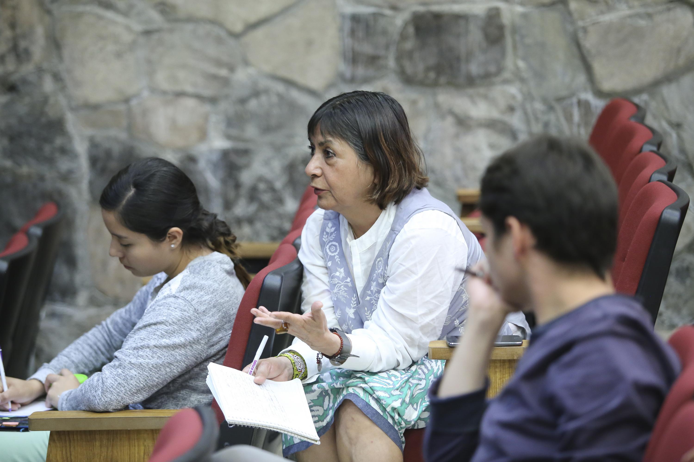 Mujer que es parte de la audiencia, participando en la discusión durante la reunión.