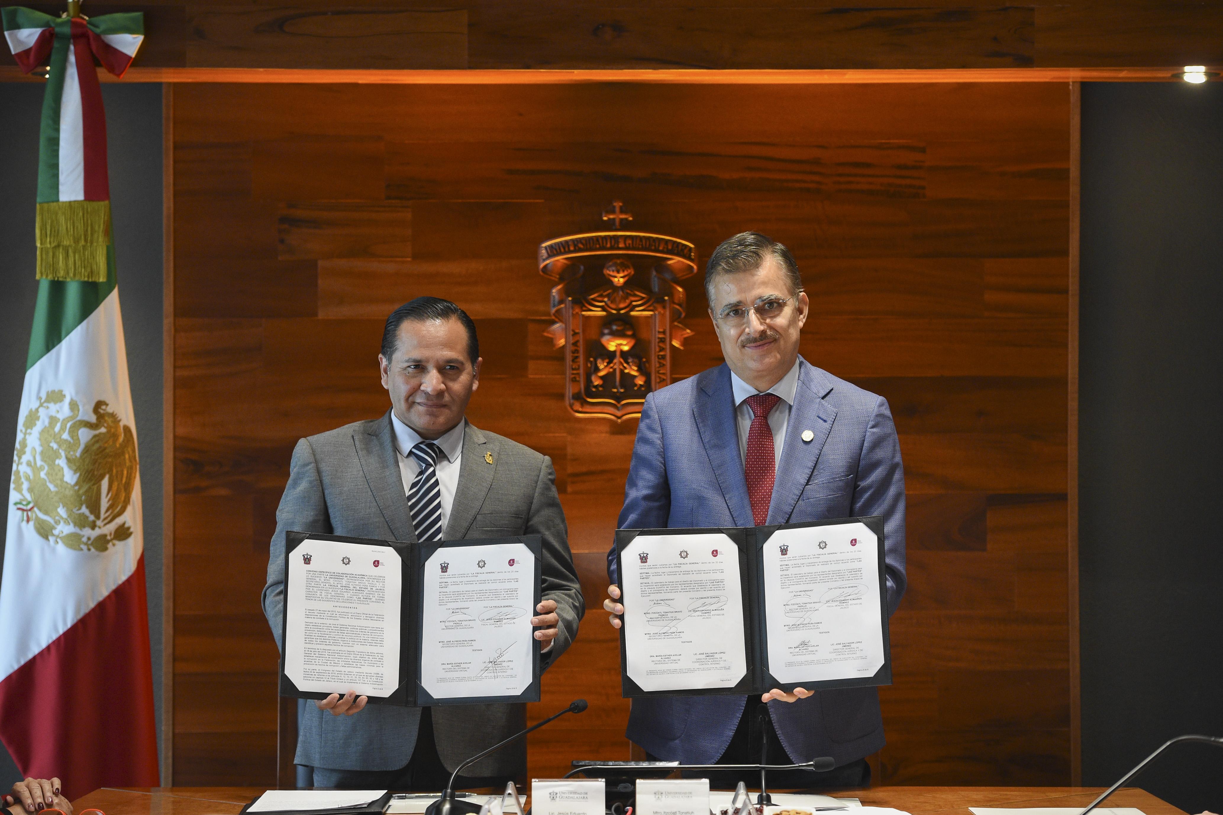 Rector General de la UdeG, maestro Itzcóatl Tonatiuh Bravo Padilla y el Fiscal General del Estado, licenciado Jesús Eduardo Almaguer Ramírez mostrando firma de convenio