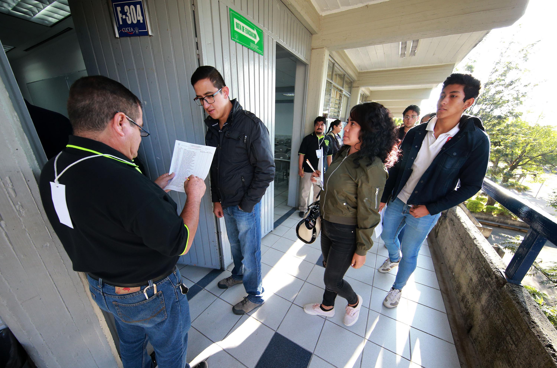 En la entrada de aulas, toman lista a los aspirantes para ingresar