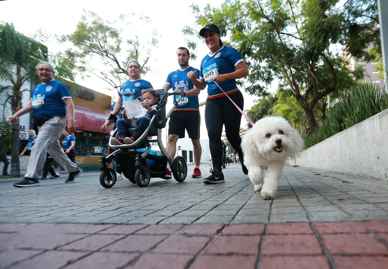 Una familia competidora de la carrera Leones Negros, llevan a un bebé en carreola y a su mascota