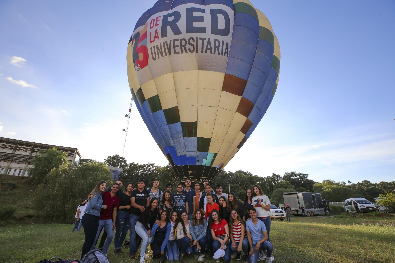 Estudiantes de CUAltos posan con el globo aerostático en el Festival Regional con motivo de los 25 años de la Red Universitaria