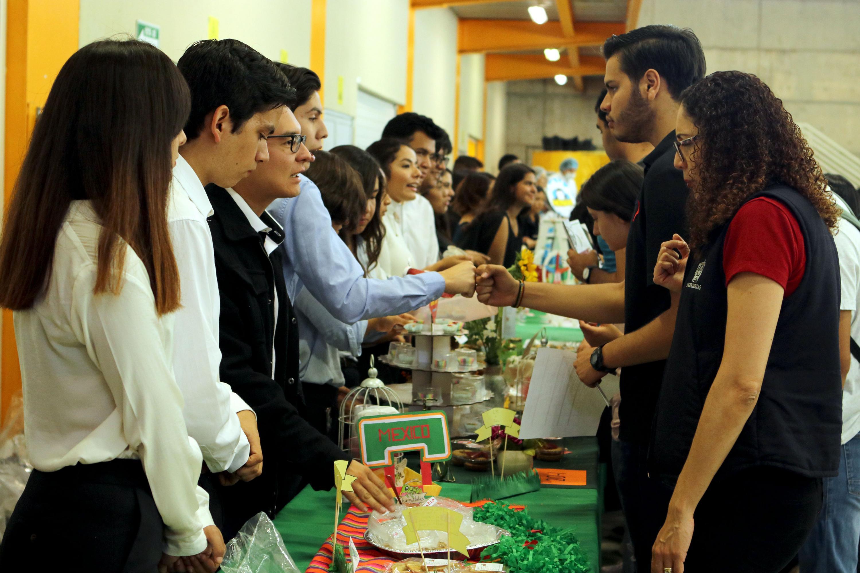 Durante la exposición de ciencia, estudiantes de la carrera de Ingeniería de Alimentos y Biotecnología, muestran mermeladas deshidratadas, popotes que se convierten en bebidas o cajetas de frijol