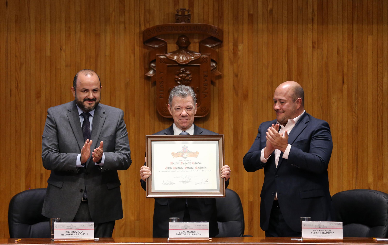 Muestra el expresidente de Colombia el reconocimiento en el Paraninfo. Lo flanquean el Rector General de la UdeG y el Gobernador de Jalisco