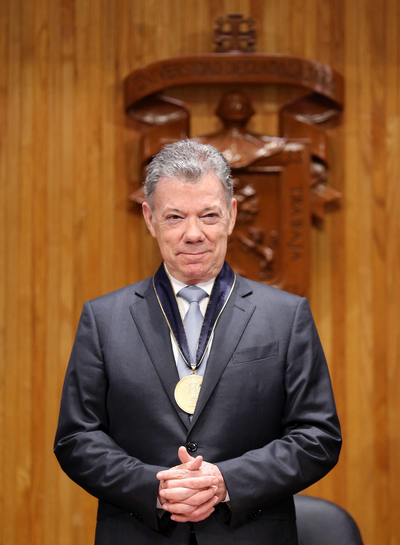 El ex presidente de Colombia, se muestra complacido y tiene puesta la medalla del Doctorado Honoris causa
